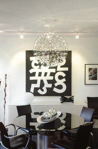In the dining room, black chairs by French designer Philippe Starck surround a Vignelli table, which features a gray glass  top and silver leaf base. A Moooi Raimond  light fixture filled with LED lights hangs over the table. The art on the wall is an acrylic on canvas by internationally recognized artist Ulfert Wilki.