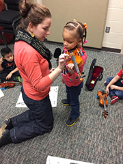 An instructor shows a young musician finger placement on a violin during a music lesson.