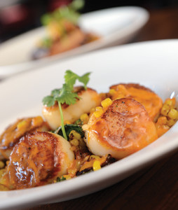 Robust poblano whipped potatoes, bacon-sauteed kale, and a cherry tomato and olive oil-based sauce provide refined touches to the tender scallops.