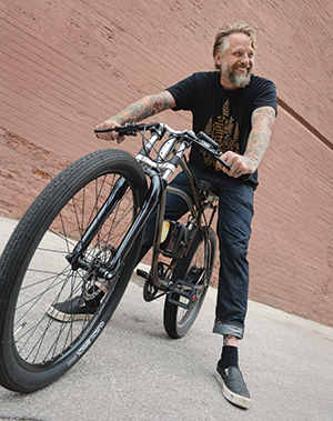 Dan Koenig shows off one of his custom-made electric bicycles, which are powered by a small battery-driven motor.