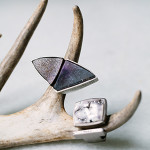 """Rings like these show why Marisa Adamson thinks of her jewelry as """"mini-sculptures."""" On the left, purple and black druzy tourmaline quartz is formed into a triangle. The ring on the right is made out of palladium with white diamonds and platinum valley agate."""